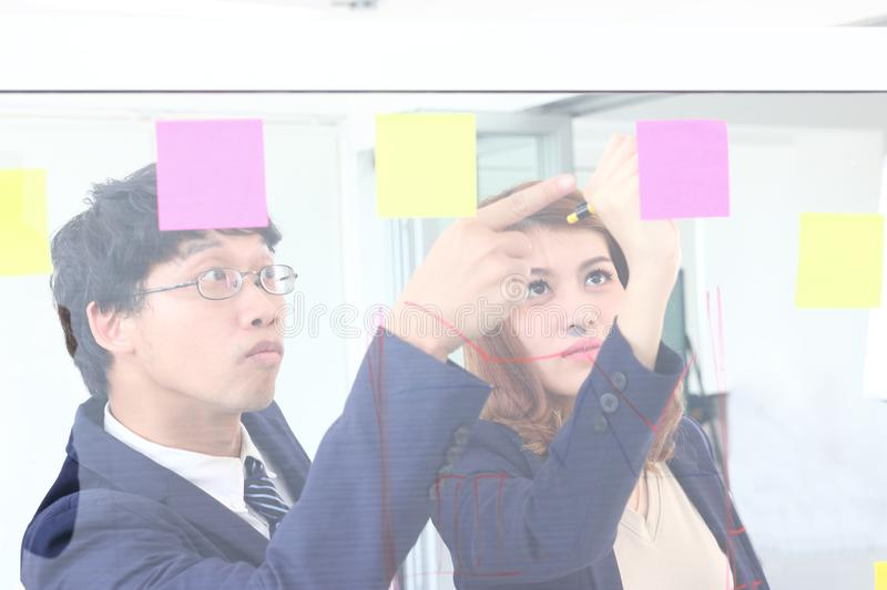 Young Asian business people use post it notes on glass wall to share idea at meeting room. Teamwork and brainstorm concept royalty free stock images
