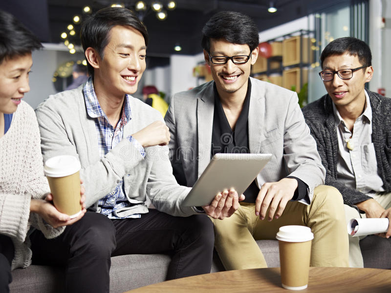 Young asian business people using tablet in office stock photos