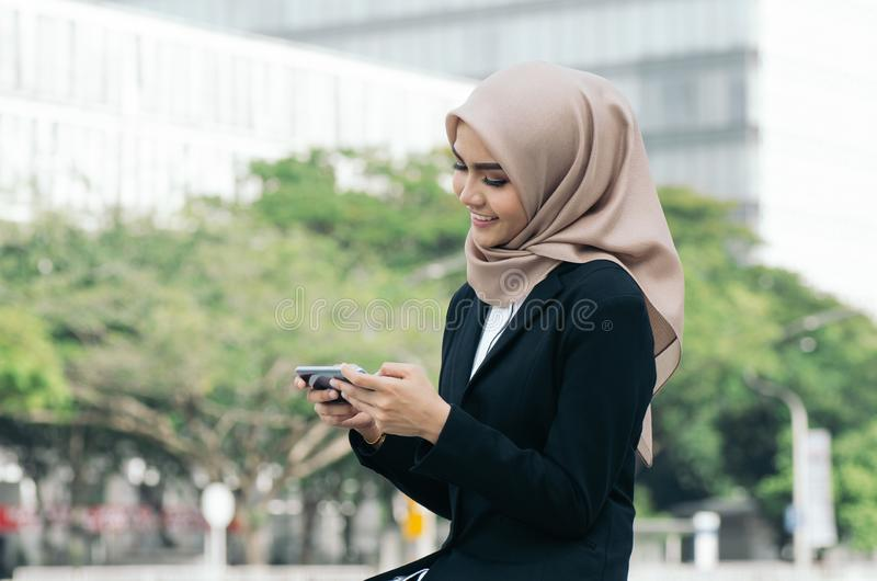 Young asian business woman on black suit sitting outside, using mobile phone royalty free stock photo