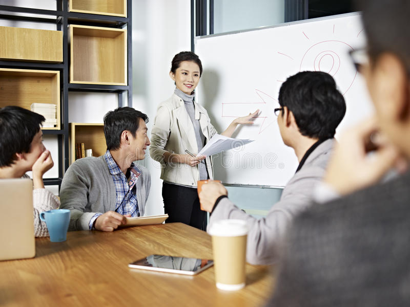 Young asian business woman facilitating a discussion. Young asian business executive facilitating a discussion or brainstorm session in meeting room stock photo