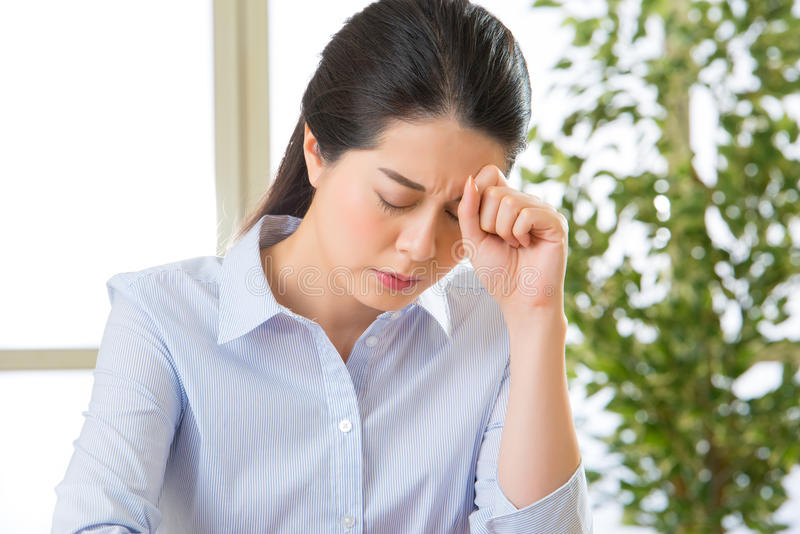 Young asian business woman with headache royalty free stock image