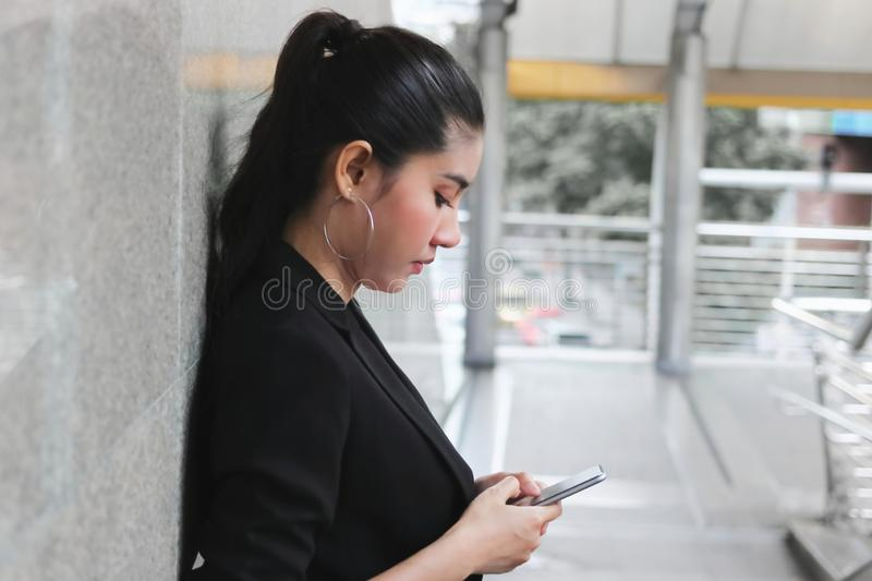 Young Asian business woman with mobile smart phone in urban background. Internet of things concept.  royalty free stock photos