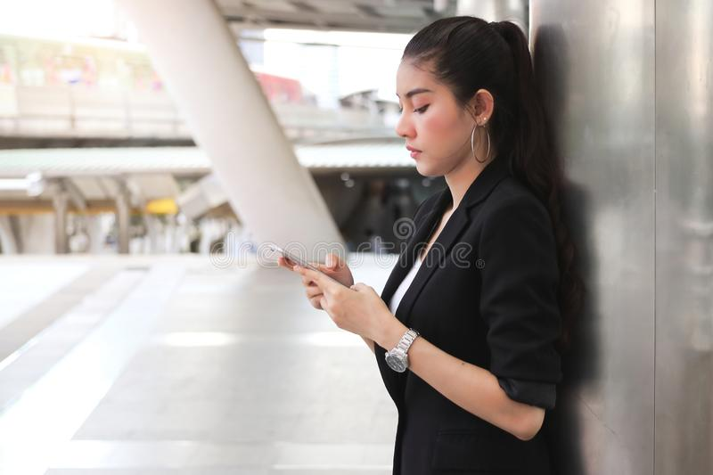 Young Asian business woman with mobile smart phone in urban background. Internet of things concept stock photos
