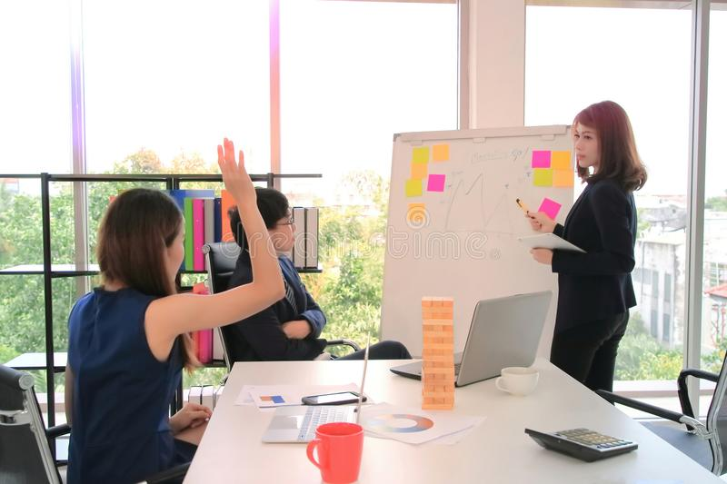 Young Asian business woman presentation on flip chart to colleague during meeting in conference room. royalty free stock photography