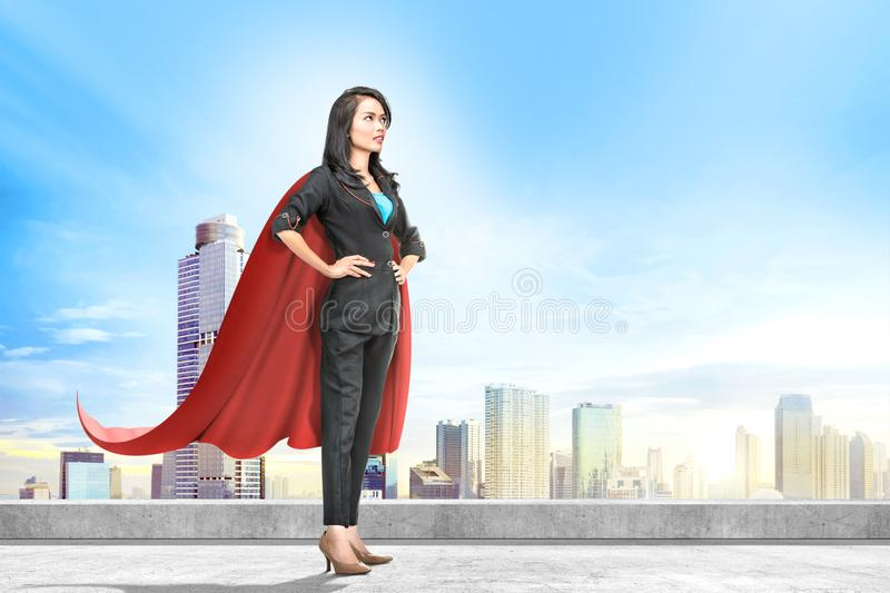 Young asian business woman with red cape standing on the rooftop royalty free stock photo