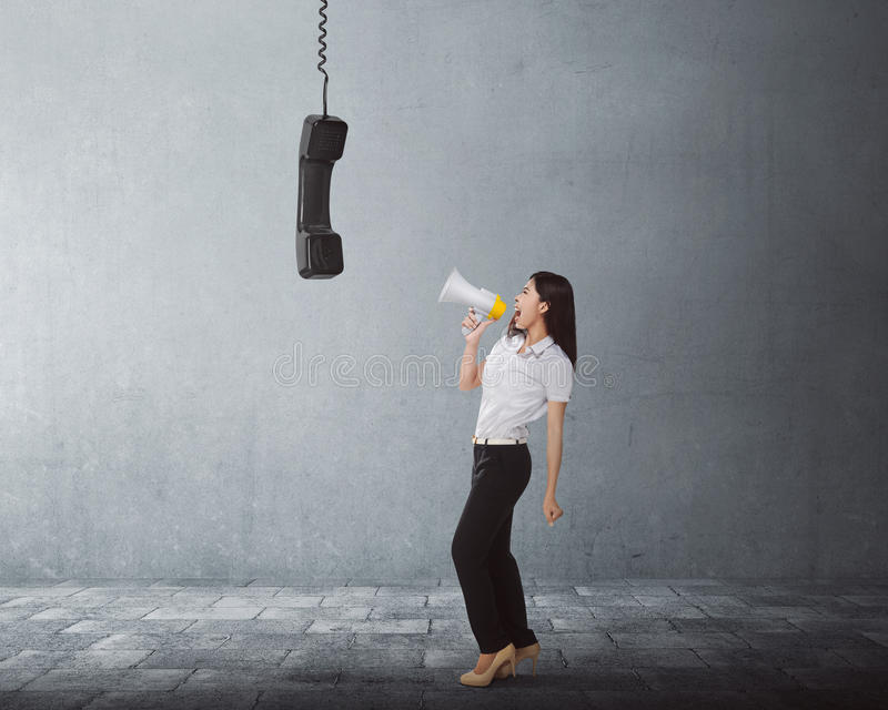 Young asian business woman screaming using a megaphone to black stock photo