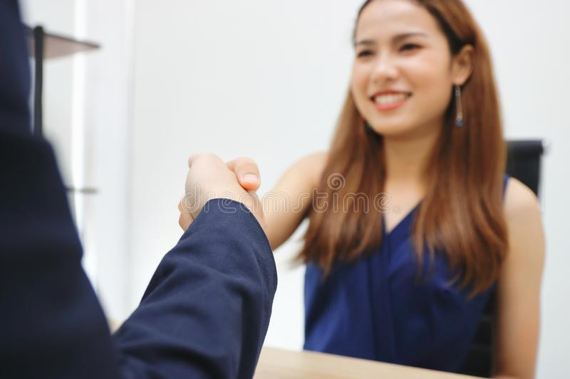Young Asian business woman shaking hands with partners after finishing a meeting. Handshake greeting deal concept. Young Asian business woman shaking hands with royalty free stock images