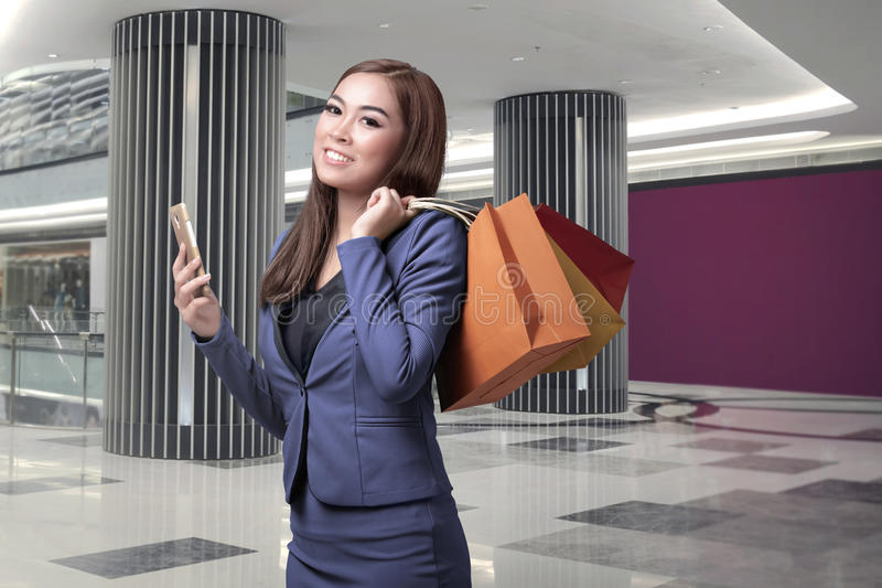Young asian business woman with shopping bags holding mobile phone stock images