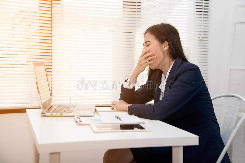 Young Asian business woman dozy on the desk in office because tired overworked. royalty free stock images