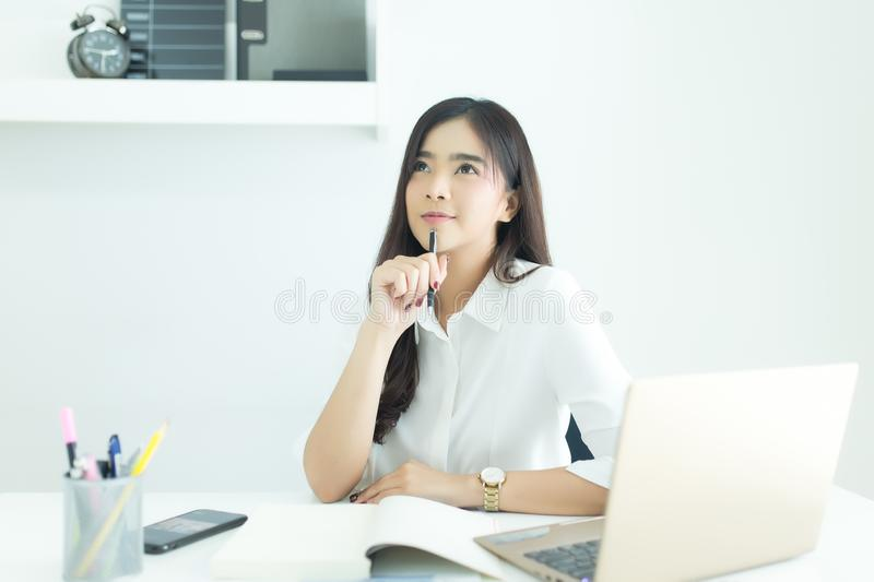 Young asian business woman smiling and thinking idea about work at desk in modern office. Young asian business woman smiling and thinking idea about work at stock photo