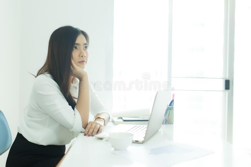 Young asian business woman smiling and thinking idea about work at desk in modern office. Young asian business woman smiling and thinking idea about work at royalty free stock images