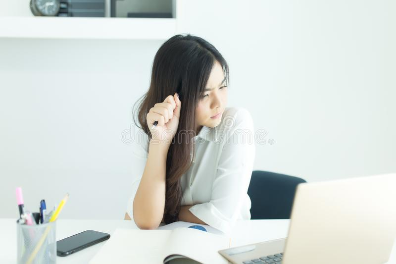 Young asian business woman smiling and thinking idea about work at desk in modern office. Young asian business woman smiling and thinking idea about work at royalty free stock photo