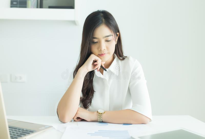 Young asian business woman smiling and thinking idea about work at her desk in modern office. Young asian business woman smiling and thinking idea about work at stock photography