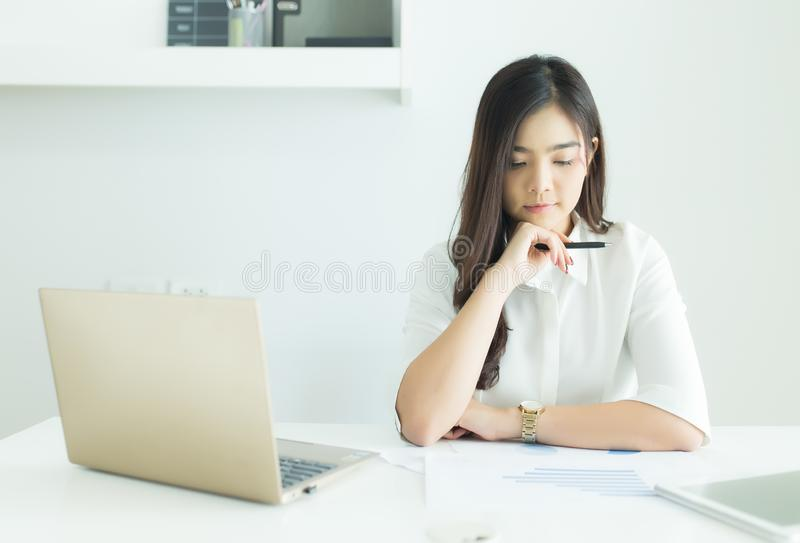 Young asian business woman smiling and thinking idea about work at her desk in modern office. stock photo