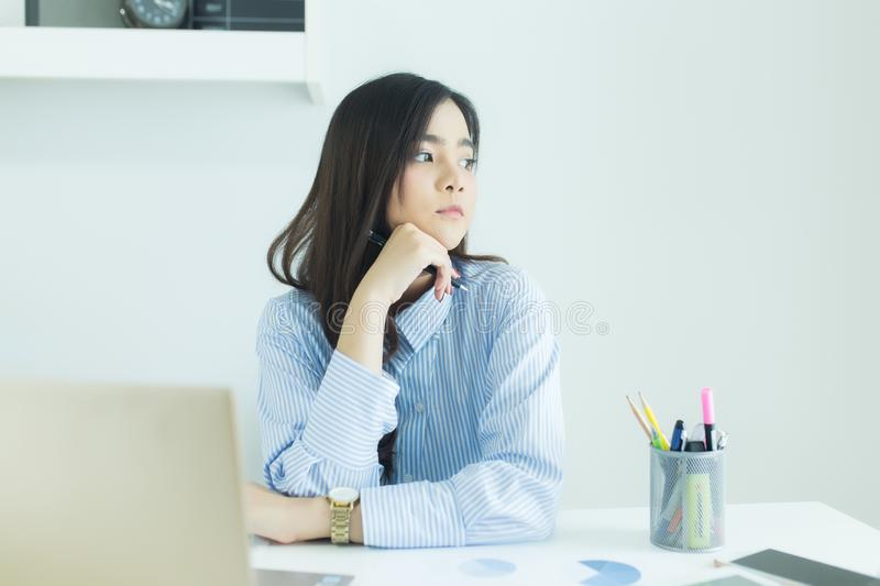 Young asian business woman smiling and thinking idea about work at her workplace. Young asian business woman smiling and thinking idea about work at her stock photo