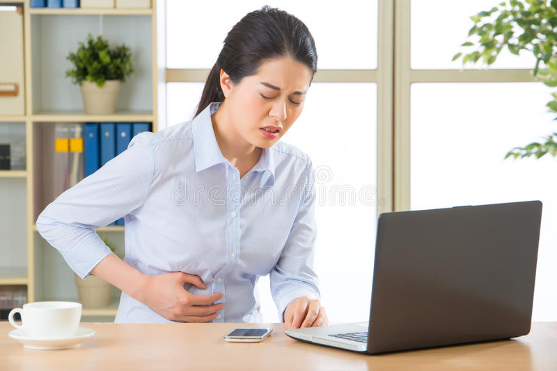 Young asian business woman with stomachache stock image