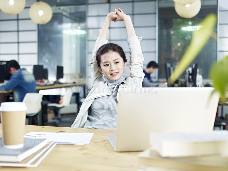 Young asian business woman stretching in office royalty free stock photography