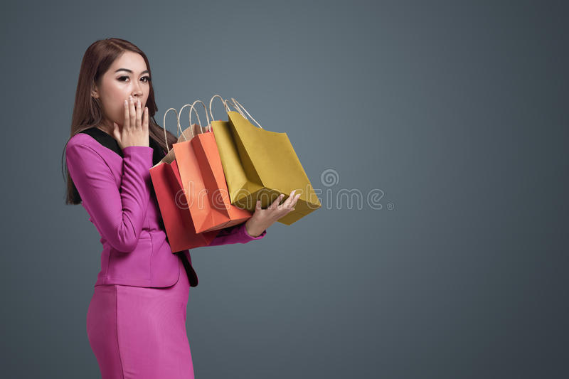 Young asian business woman surprised holding many paper bag in h royalty free stock image