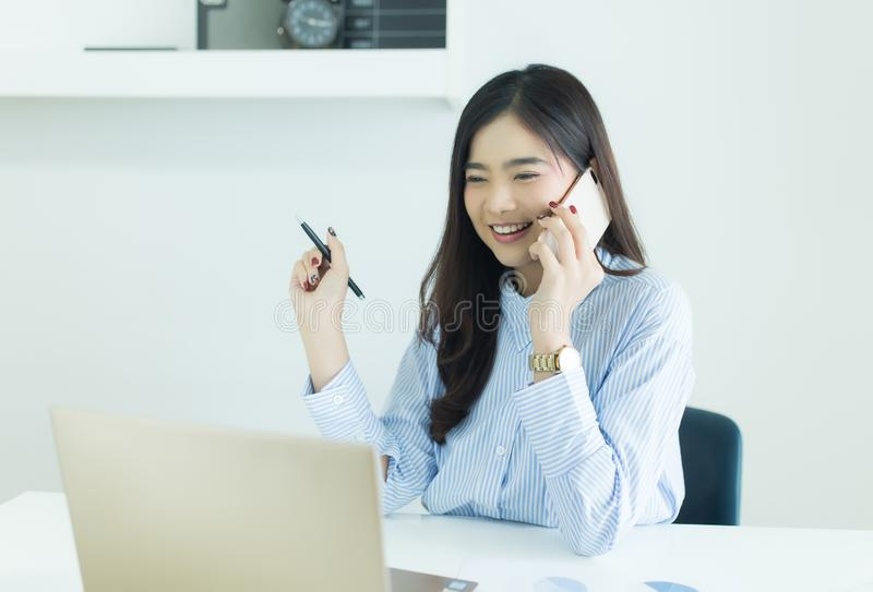 Young asian business woman talking on the mobile phone and smiling at her work place in office and looking at laptop. royalty free stock image