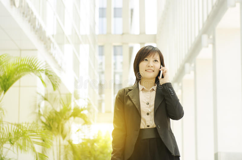 Young Asian business woman talking on phone stock photo