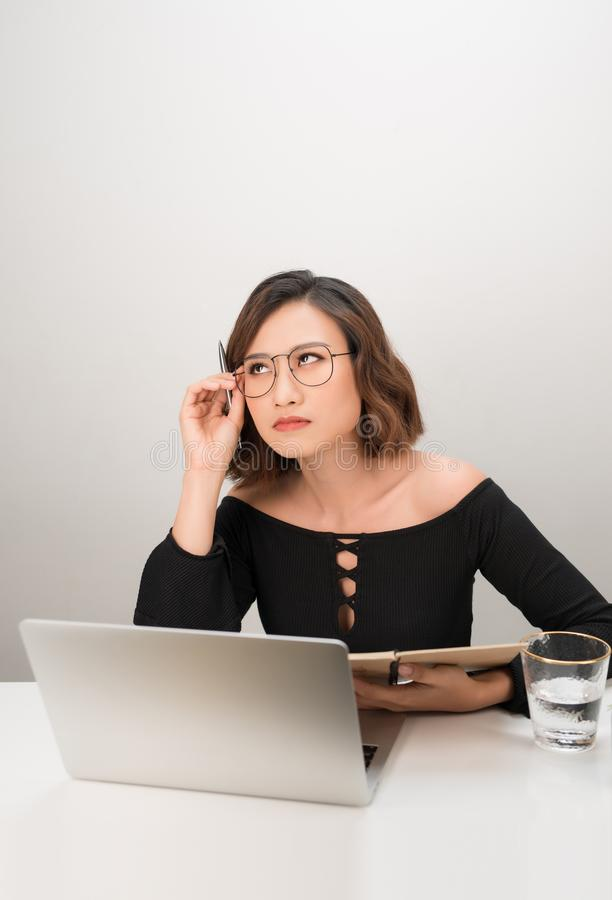 Young asian business woman thinking daydreaming sitting at desk with laptop computer royalty free stock images