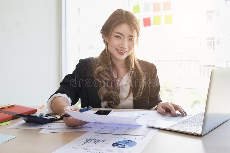 Young asian business woman using laptop computer and cell phone stock photography