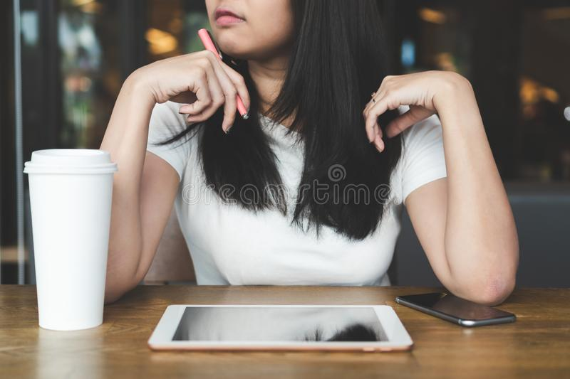 Young asian business woman working with tablet laptop, phone and stock photos