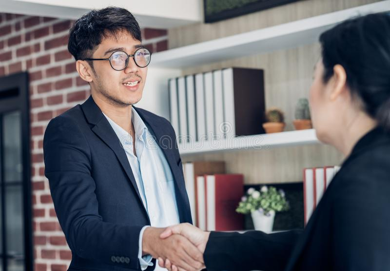 Young asian businessman and businesswoman handshake about business agreement at meeting table in modern office.business royalty free stock image