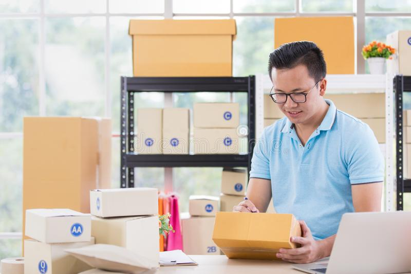 Young Asian businessman in casual shirt write on parcels, working in simple house office look like doing startup business. royalty free stock photos