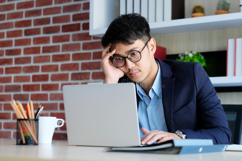 Young asian businessman concentrate on working with laptop computer at office, Asian office man comtemplate on working with laptop royalty free stock photo