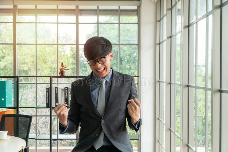 Young Asian businessman excited happy and celebrating success in the workplace after see finalizing the annual sales report. Conce stock images