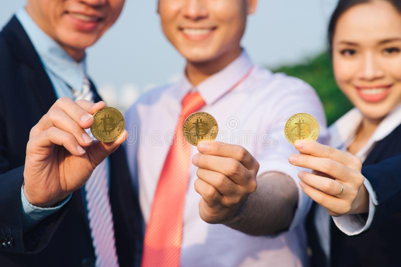 Young Asian Businessman holding golden bitcoin in front of his international Multi ethnic team in modern city stock photo