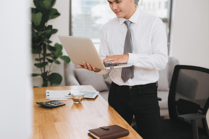 Young asian businessman holding a laptop pc royalty free stock photos