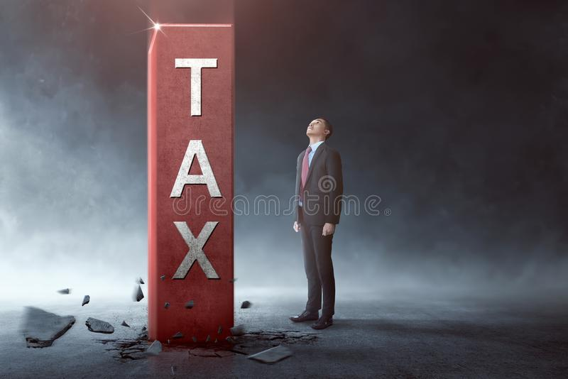 Young asian businessman looking at high tax block royalty free stock photography