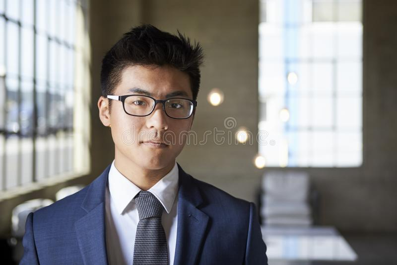 Young Asian businessman looking to camera, head and shoulders stock photos