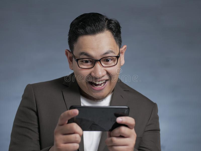 Young Asian Businessman Playing Games on Tablet Smart Phone royalty free stock image