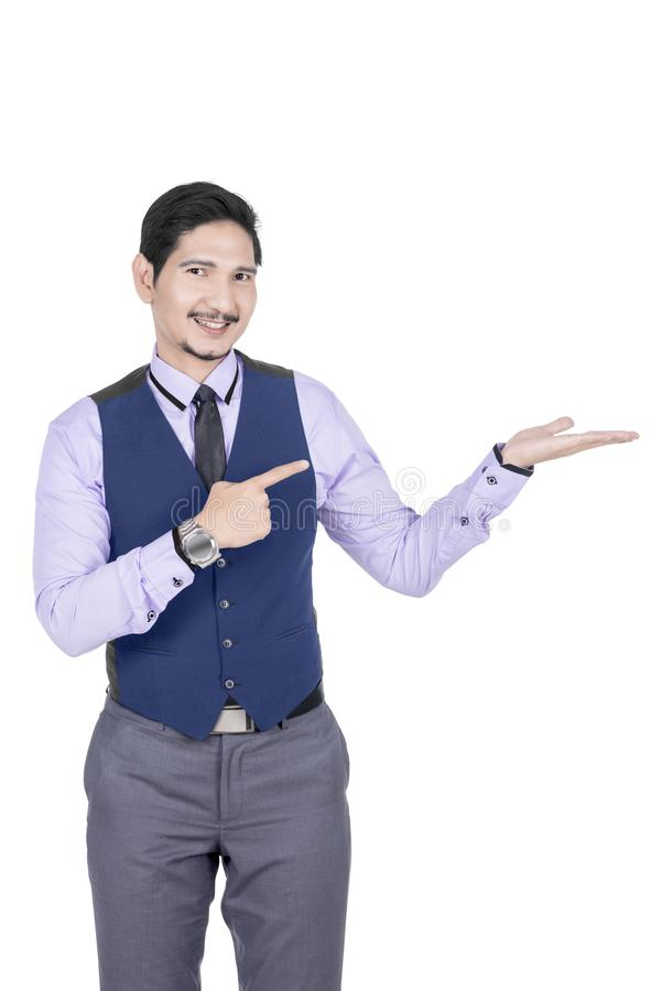 Young asian businessman pointing his open palm. Posing isolated over white background stock photography