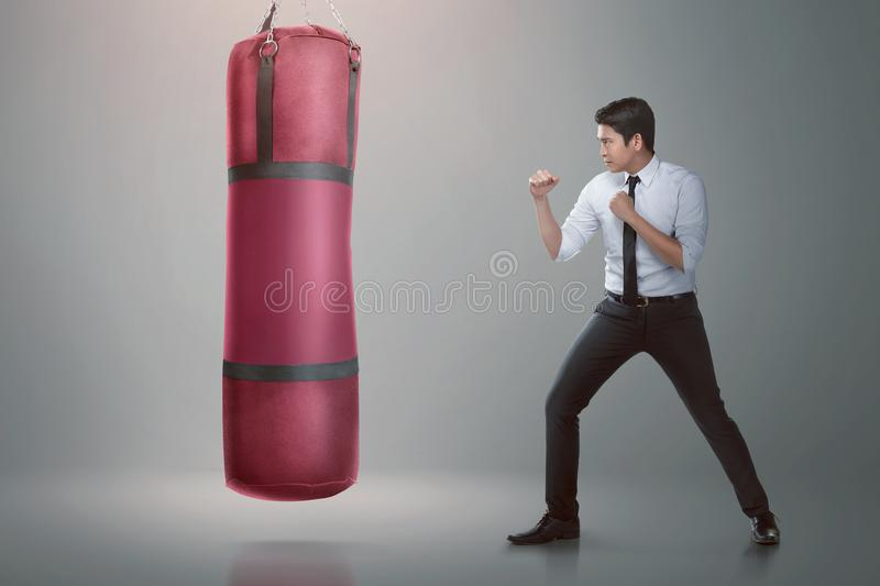 Young asian businessman punching boxing bag. Over gray background stock image