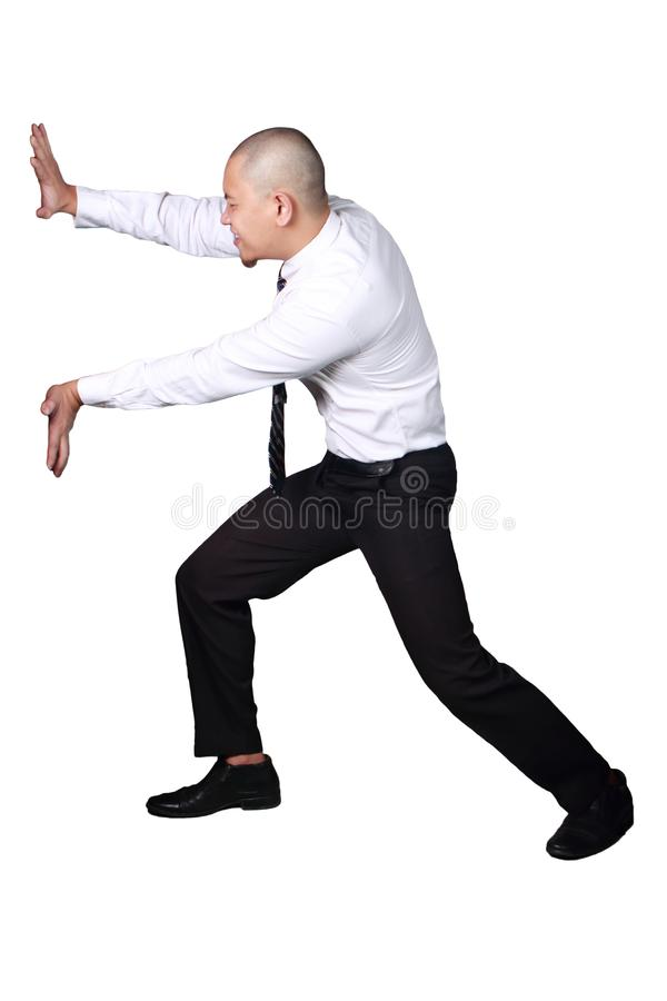 Young Asian Businessman Pushing or Withstand Something Gesture. Young businessman wearing white suit and black pants pushing or withstand gesture. Isolated on stock images