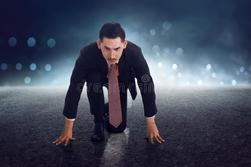 Young asian businessman in start position getting ready for run stock photos