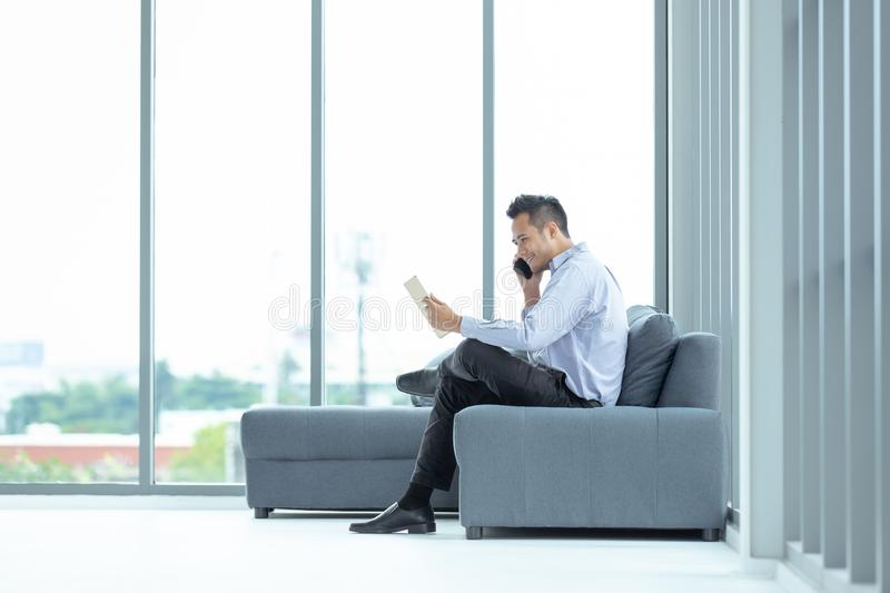 Young Asian businessman using mobile phone sitting on sofa. Happy smile and have tablet at hand. The big window in the modern stock photos