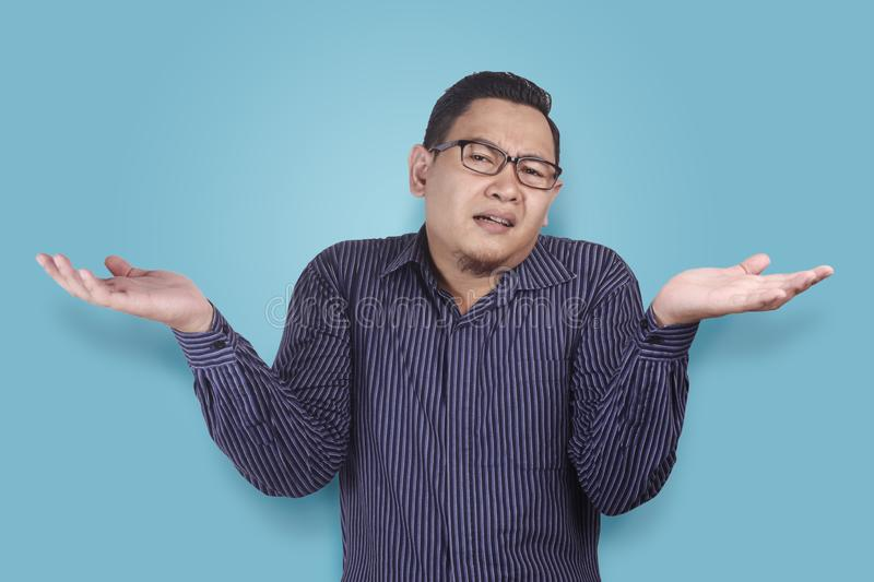 Young Businessman Indifferent Gesture. Young Asian businessman wearing blue shirt indefferent gesture. Close up body portrait indonesian malay thai chinese royalty free stock photos
