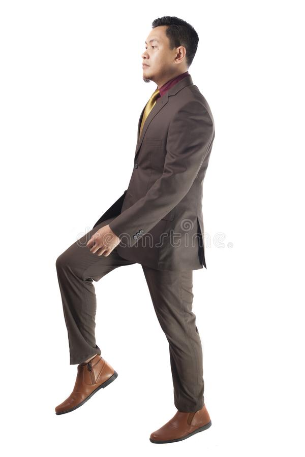 Young Asia Businessman Walking, Stepping Up, Side View royalty free stock photography