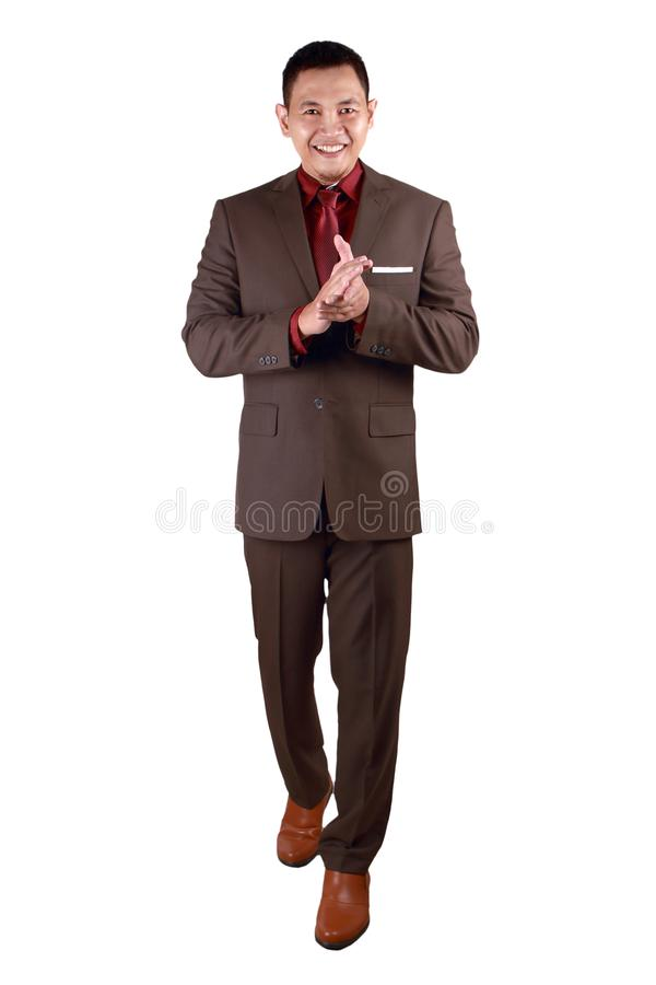 Happy Young Businessman Clapping Hands. Young Asian businessman wearing brown suit, proud clapping gesture. Isolated on white. full body portrait achievement royalty free stock photography