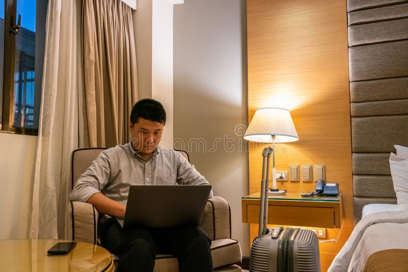 Asian businessman working late in hotel room. Young Asian businessman working late in hotel room stock image