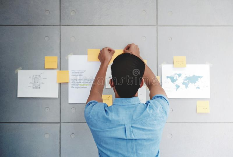 Young Asian Businessman Working in Office Meeting Room. Man Analyzing Data Plans and Project. Concentrate on Document Note on Board royalty free stock photography