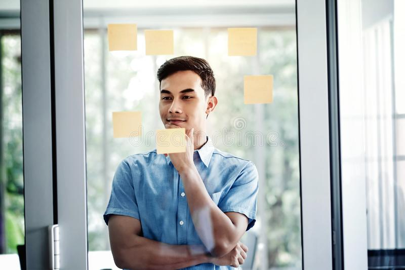 Young Asian Businessman Working in Office Meeting Room. Man Analyzing Data Plans and Project. Concentrate on Document Note on Board stock photography