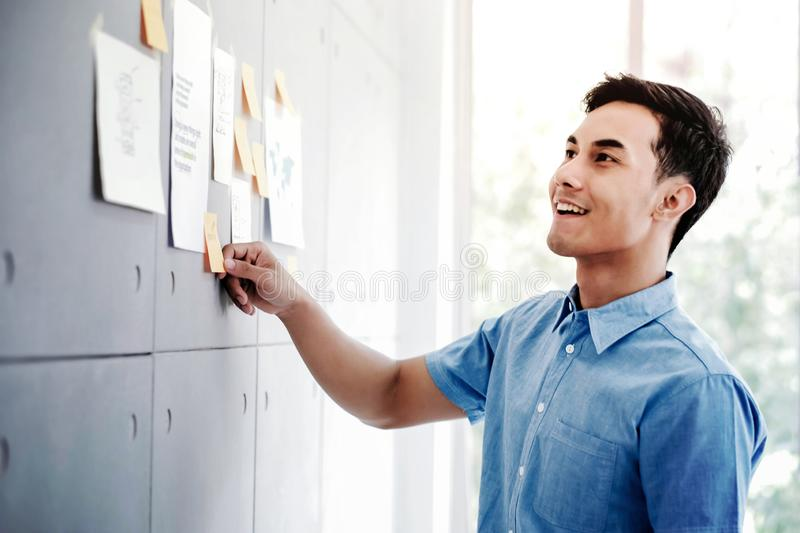 Young Asian Businessman Working in Office Meeting Room. Man Analyzing Data Plans and Project. Concentrate on Document Note on Board stock images