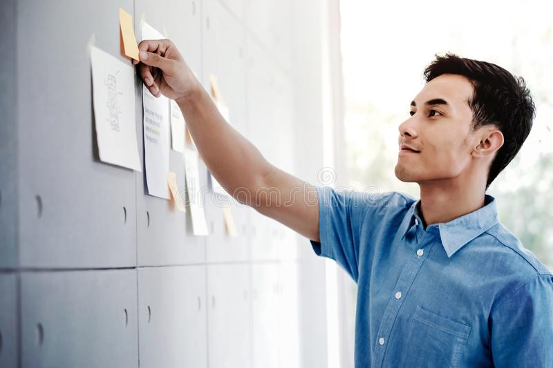 Young Asian Businessman Working in Office Meeting Room. Man Analyzing Data Plans and Project. Concentrate on Document Note on Board stock photos