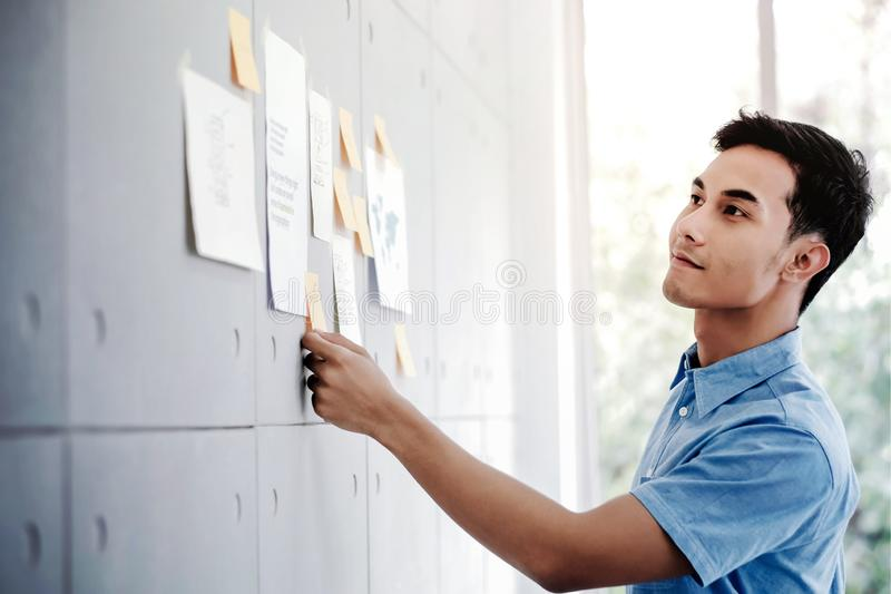 Young Asian Businessman Working in Office Meeting Room. Man Analyzing Data Plans and Project. Concentrate on Document Note on Board royalty free stock photos